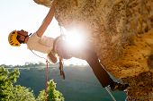 Image Of Male Climber In Helmet Clambering Up Cliff. Sunflare Effect. poster