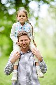 Happy man holding his adorable daughter on neck during chill in park on summer day poster