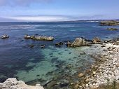 The Rocky Coastline Along Pacific Grove, California With The Blue And Teal Waters Of Monterey Bay poster