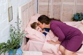 Mother Giving Good Night Kiss To Sleeping Son. Lovely Mother Putting Son To Bed. Mother Kissing Baby poster