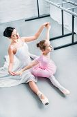 High Angle View Of Adult Ballerina Exercising With Cute Little Child In Pink Tutu In Ballet School poster