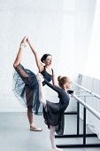 Side View Of Young Ballet Teacher And Little Student Stretching Together In Ballet School poster