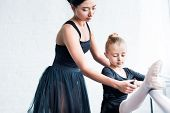 Cropped Shot Of Young Ballet Teacher Training Child In Ballet School poster