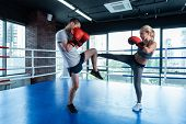 Husband And Wife. Dark-haired Strong Athletic Man Working Out On Boxing Ring With His Appealing Wife poster