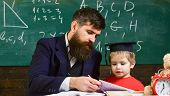 Kid Studies With Teacher, Near Copybook, Clock, Toy. Teaching Kid Concept. Teacher And Pupil In Mort poster