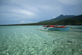 stock photo of camiguin  - traditional banka outrigger boat in clear waters of camiguin island in the philippines - JPG