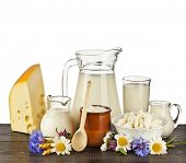 dairy products on the wooden board table on white background