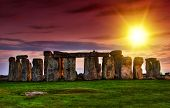stock photo of stonehenge  - Fantasy sunset at Stonehenge with dramatic sky and sun rays - JPG