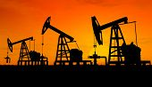 foto of oil rig  - Three pumps over orange sky  - JPG