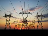 stock photo of electrical engineering  - 3D Electric powerlines over sunrise  - JPG