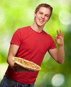 portrait of a young man holding a pizza and doing a good gesture against a nature background