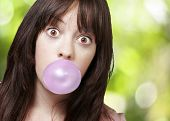 young girl with a pink bubble of chewing gum against a nature background