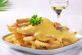 Gegrilltes Fischfilet in Käse-Teig und Chips auf einem weißen Teller