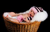 Newborn Child in a wicker basket on a black background.