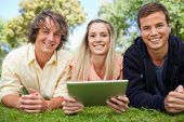 Three smiling students using a tactile tablet while lying in a park