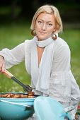 Portrait of an attractive woman in casual wear cooking food on portable barbecue