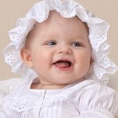 closeup portrait of little child baby girl  smiling in white clothing hat face