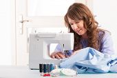 stock photo of thread-making  - Beautiful young woman using sewing machine at home with reels of thread - JPG