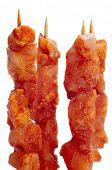 primer plano de algunos crudo Español pinchos morunos, pinchos de carne de pollo con especias, sobre un fondo blanco
