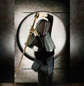 Portrait of a young woman wearing kendo clothing and standing in martial arts stance