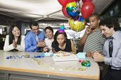 picture of office party  - Woman blowing out birthday candles at office party - JPG
