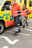 Rushing blurry paramedic team with portable devices and ambulance car
