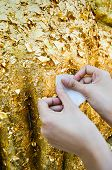 Close Up Of Buddhist's Hand Placing Gold Leaf On Buddha Statue
