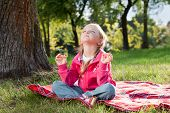 Little Girl Relaxing In Yoga Pose On Grass In A Park