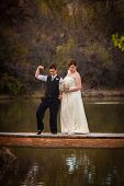 stock photo of dock a pond  - Macho lesbian groom with bride on dock over pond - JPG