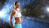 Fitness young woman standing under rain drops