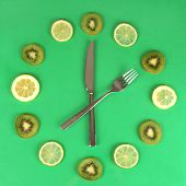 Clock made of kiwi, lime and lemon slices, on color background