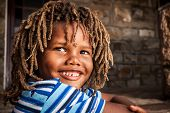 image of scabs  - young african boy with rasta hair in a blue striped shirt sitting on a stone porch smiling up in admiration - JPG