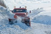 stock photo of plowing  - Machinery with snowplough cleaning road by removing snow from intercity highway after winter blizzard - JPG