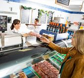 Happy saleswoman giving meat package to female customer at counter in butcher's shop