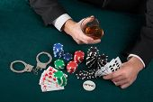 Gambler With Alcohol And Handcuffs