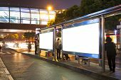 Night bus station with blank billboard