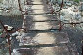 picture of luzon  - A rusty steel cable suspension bridge with a wooden plank walkway stretches across a stream near Subic Luzon Philippines - JPG