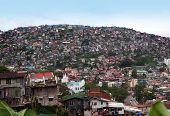 stock photo of overpopulation  - Thousands of homes and other buildings crowd the mountainsides of Baguio City - JPG