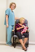 Full length portrait of nurse standing by mother feeding newborn babygirl in hospital