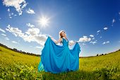 Luxury beautiful woman in long blue evening fashionable dress outdoors. In the  sunlight on a green