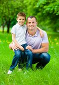 Dad keeps son on the knee in the park. Concept of happy family relations and carefree leisure time