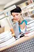Woman surrounded with piles of books reads sitting at the desk at the library
