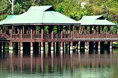 stock photo of meadowlark  - Details of Brown and Green Gazebos on Stilts Above Water - JPG