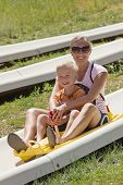 stock photo of carnival ride  - Mother and son on a alpine coaster ride - JPG