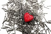 Red Heart On Pile Of Iron Nails