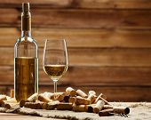 foto of merlot  - Bottle and glass of white wine on a wooden table among corks  - JPG