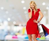 foto of boutique  - Happy smiling blond woman with shopping bags and mobile phone in shop interior  - JPG