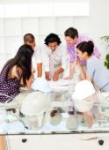 stock photo of team building  - A team of architects at the meeting looking at blueprints in the office - JPG