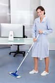 stock photo of janitor  - Portrait Of Happy Female Janitor Cleaning Floor At Office - JPG