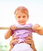 foto of daycare  - Portrait of cute little girl lifting on horizontal bar outdoors - JPG